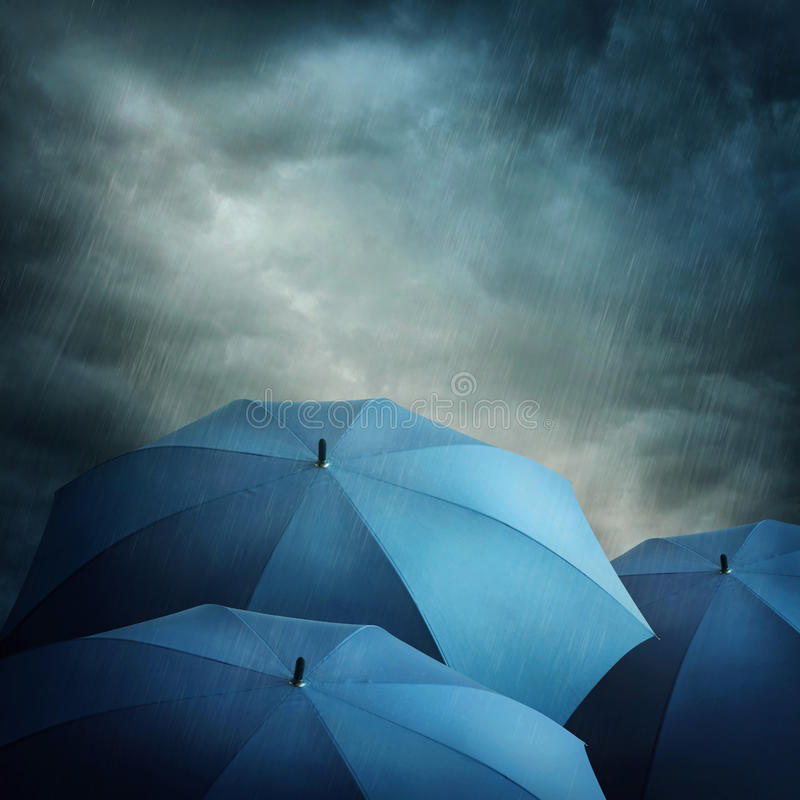 Dark clouds and umbrellas. Dark stormy clouds and umbrellas stock photo