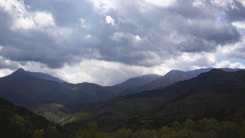 Dark cloudscape on a mountain landscape silhouette stock image