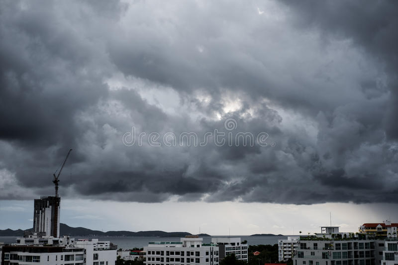 Dark cloudy storm on sky over the sea, with buildings in the city royalty free stock photo