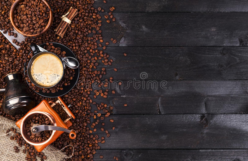 Dark coffee background, top view with copy space. Black cup of coffee, ground coffee, mill, bowl royalty free stock photos