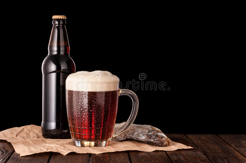 Dark cold beer in frosty mug, dry fish, brown bottle on dark woo. Dark cold beer in a frosty mug on dark wooden table. stockfish and brown bottle on paper stock photography