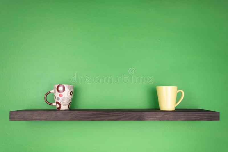 A dark color shelf with texturing wood is installed on a green wall; on the shelf there are two differently colored mugs.  royalty free stock photography