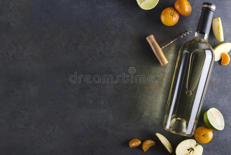 Dark colors, shining lights.Bottle of white wine surrounded by delicious and juicy fruits on the rustic surface.Top view and empty stock image