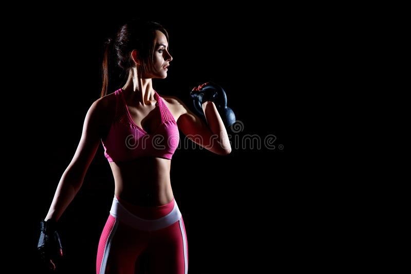 Dark contrast photo of young beautiful fitness woman which training in gym. Working out with dumbbells on black background stock photos