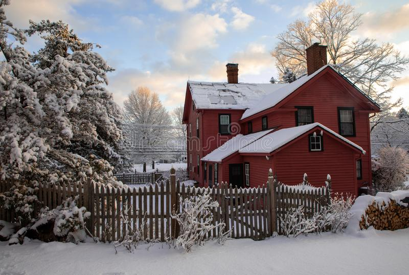 Dark coral painted 18th century New England clapboard home on snowy day at dawn stock photography