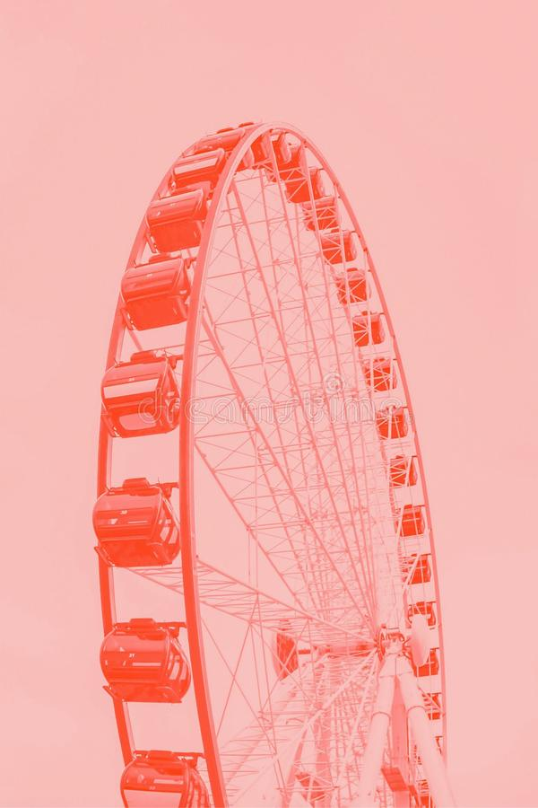 Dark coral pink ferris wheel on a light coral color background stock image