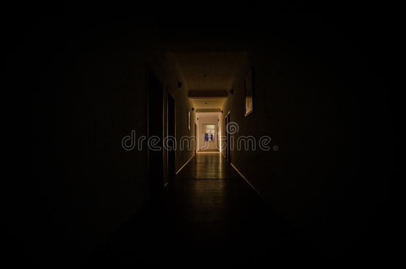 Dark corridor with cabinet doors and lights with silhouette of spooky horror man standing with different poses. royalty free stock photography