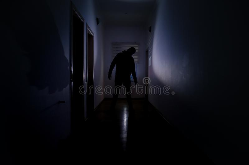 Dark corridor with cabinet doors and lights with silhouette of spooky horror man standing with different poses. royalty free stock images