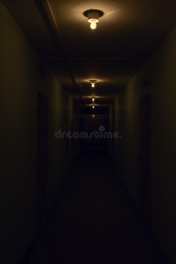 Dark corridor with glowing lamps stock image
