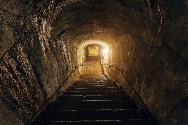 Dark corridor of old abandoned underground Soviet military bunker. Staircase goes down royalty free stock images