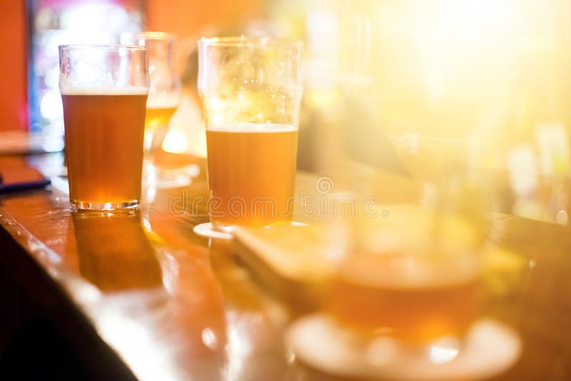 Dark craft beer on the bar. Copy space. Friday party evening. 2 Half-empty glasses of alcohol royalty free stock photos