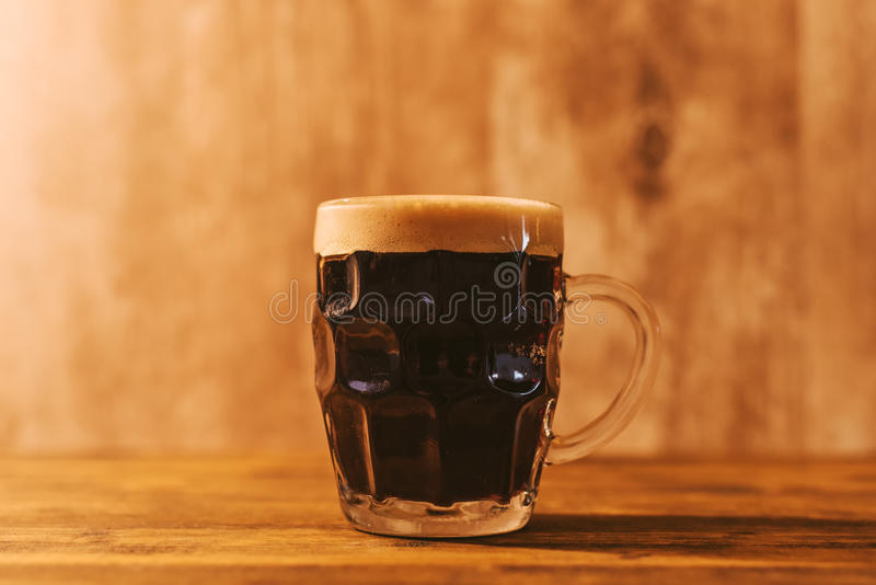 Dark craft beer in british dimpled glass pint mug royalty free stock photos