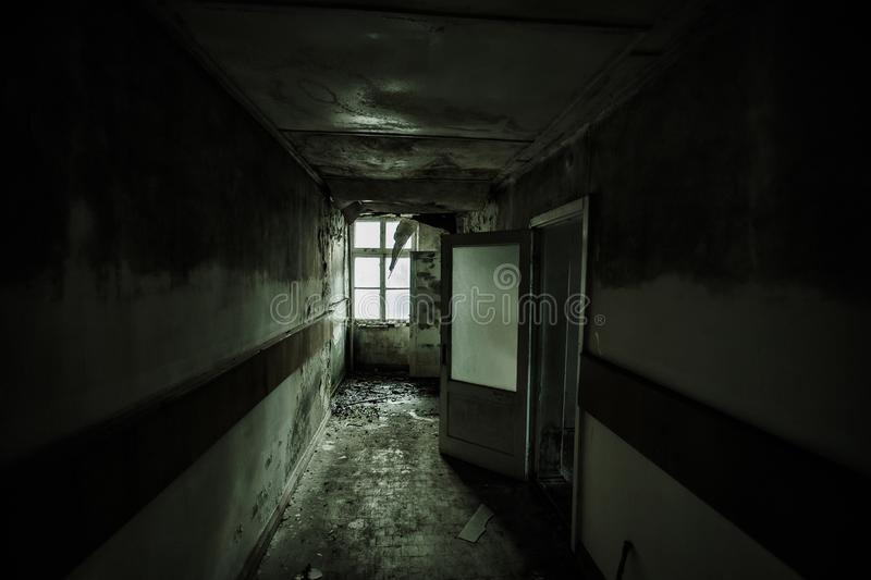 Dark and creepy corridor of abandoned building royalty free stock photo