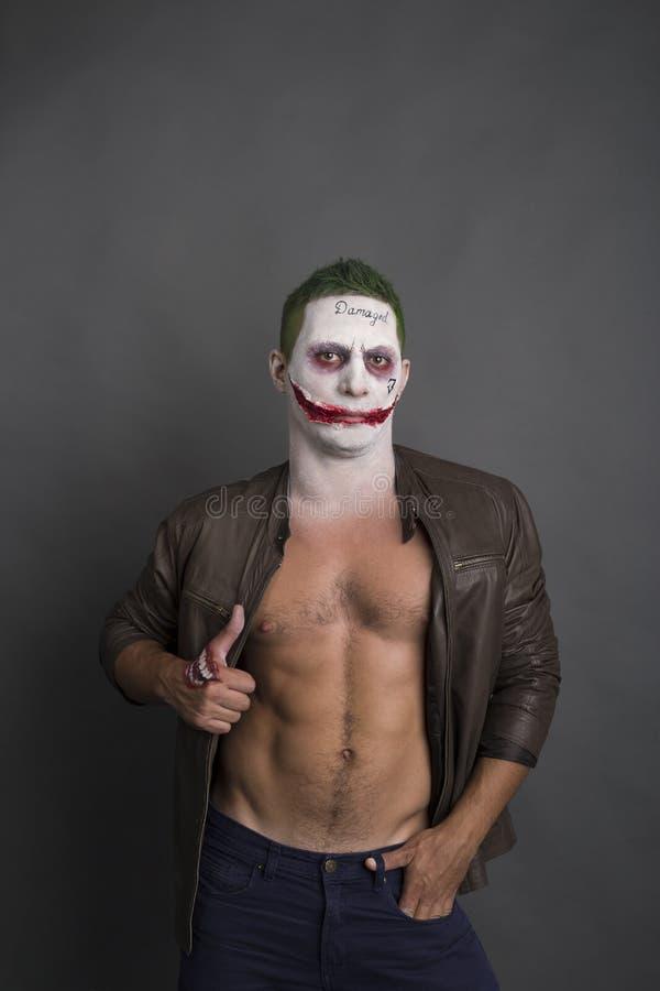 Dark creepy joker face screaing angry. green hair royalty free stock image