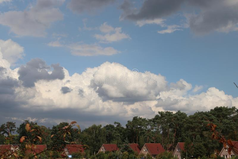 Dark cumulonimbus clouds above trees and houses to become bad weather in the Netherlands royalty free stock images