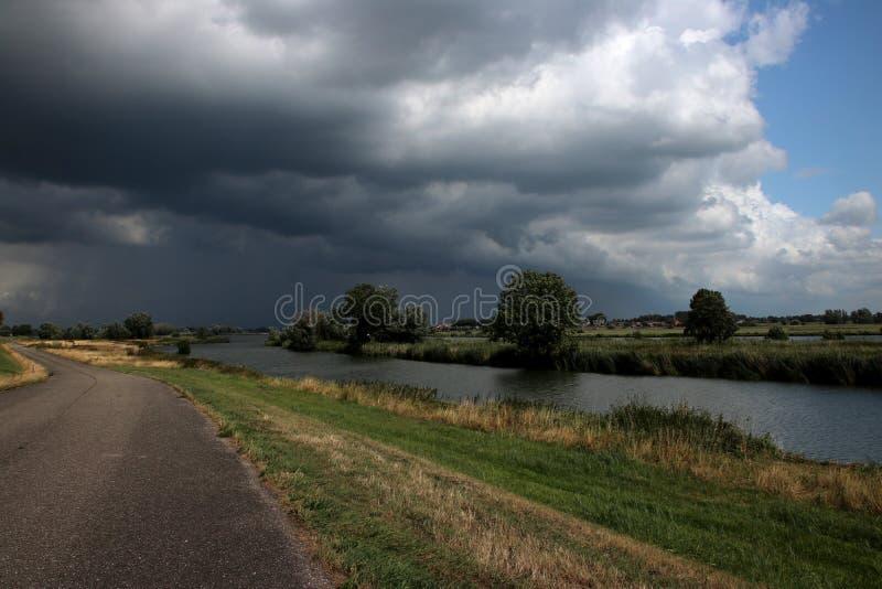 Dark cumulusclouds over river the IJssel at Kampen in Netherlands stockfoto