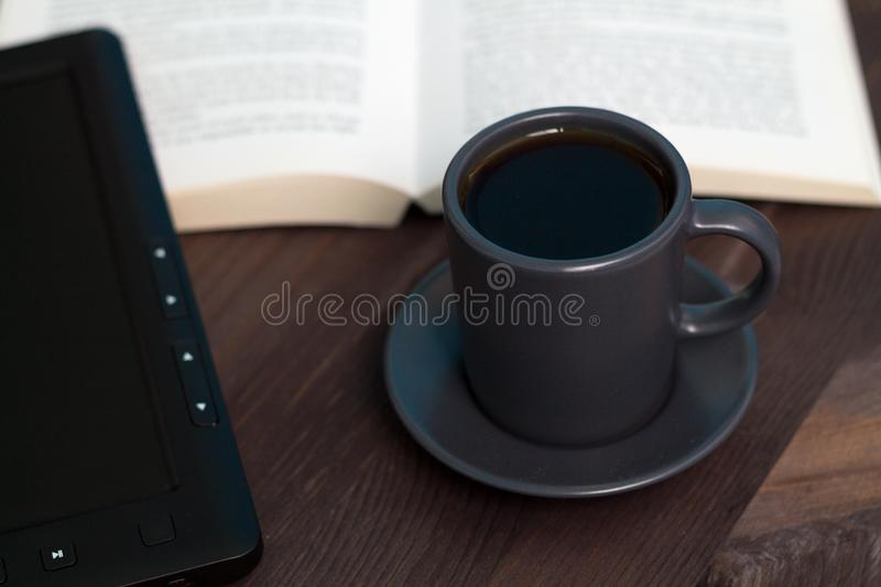 Dark cup of coffee and black notebook on a wooden table stock photos