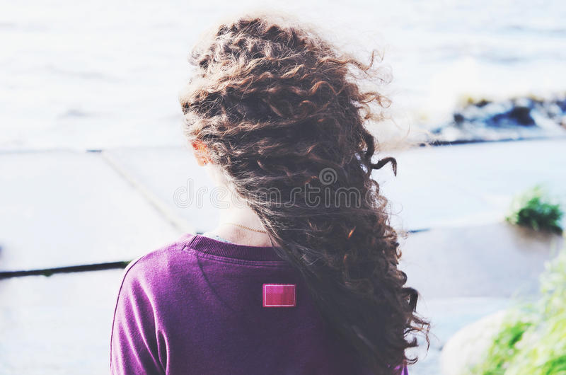 Dark curly hair woman on the beach. Back view royalty free stock image