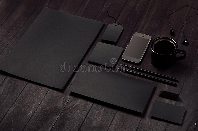 Dark deluxe black branding stationery, mockup scene with phone, coffee on black wooden plank. royalty free stock photo