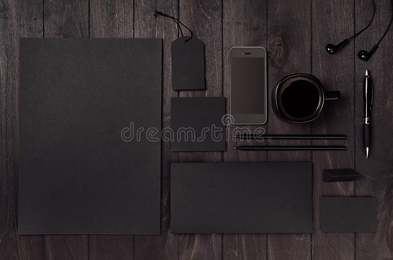Dark deluxe black branding stationery, mockup scene with phone, coffee on black wooden plank. stock photography