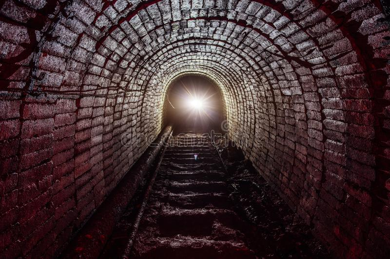 Dark dirty abandoned uranium mine with rusty remnants of railway.  stock images