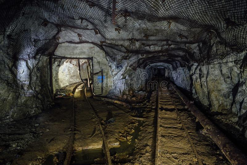 Dark dirty abandoned uranium mine with rusty remnants of railway, Bifurcation of tunnel. Dark dirty abandoned uranium mine with rusty remnants of railway royalty free stock photography