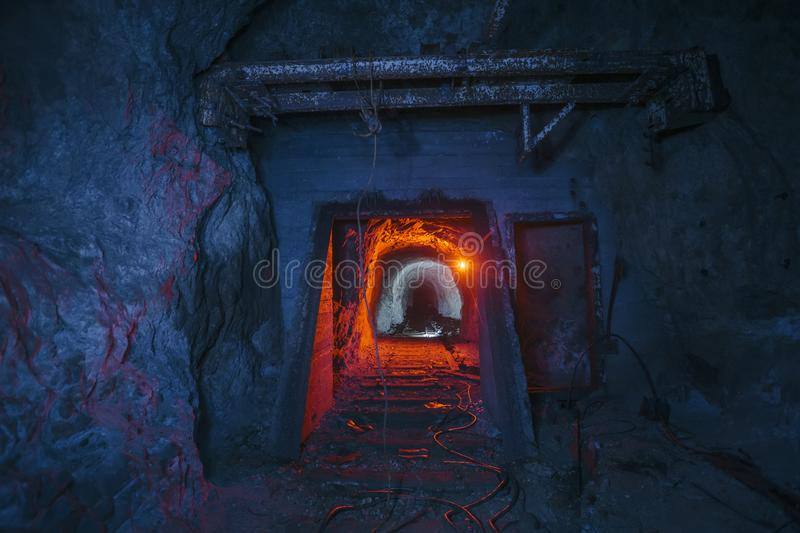 Dark dirty abandoned uranium mine with rusty remnants of railway color illuminated.  stock images