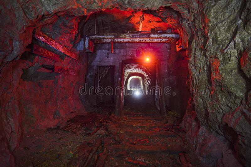 Dark dirty abandoned uranium mine with rusty remnants of railway color illuminated.  stock photo