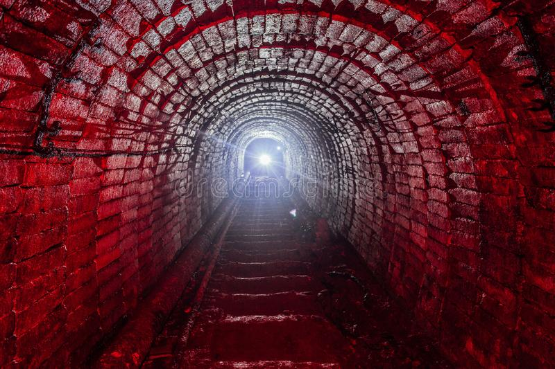 Dark dirty abandoned uranium mine with rusty remnants of railway illuminated by red light.  royalty free stock photo