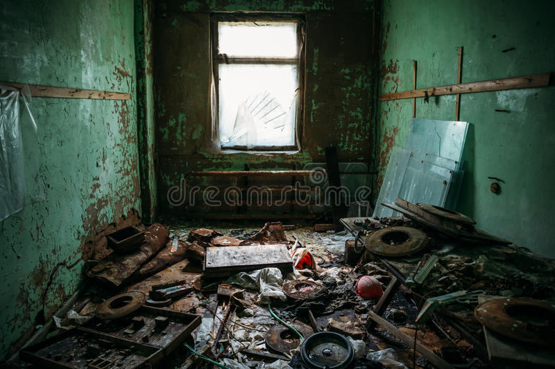Dark dirty room with garbage in an abandoned industrial building royalty free stock images