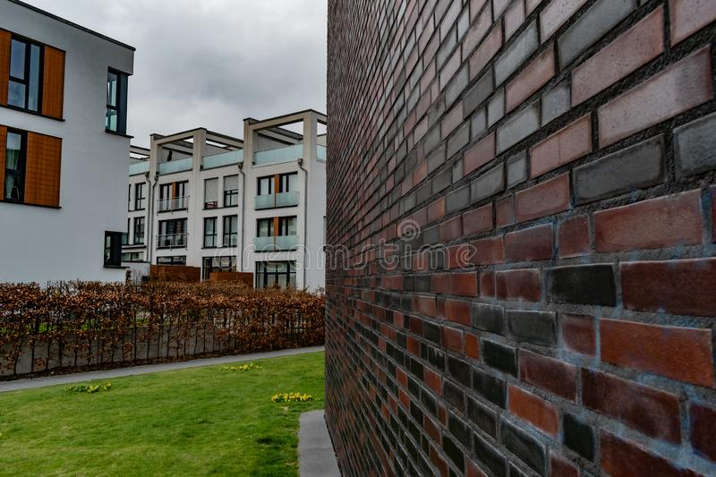 Dark earth tone bricks lead to new style apartment complex royalty free stock image