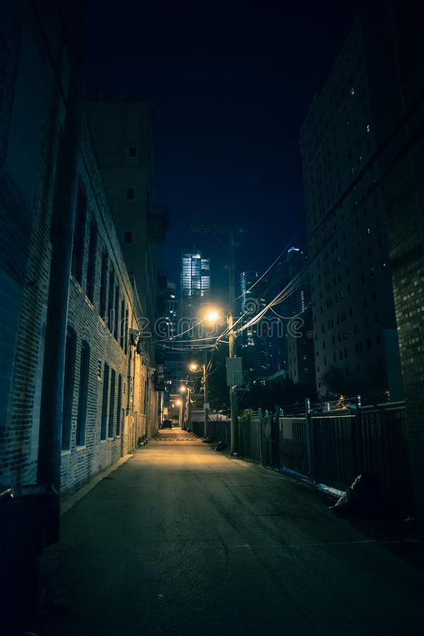 Dark and eerie city alley at night stock photography