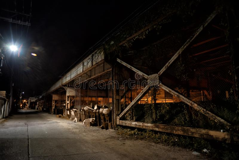 Dark and eerie urban city alley at night. Dark and eerie urban city alley with a vintage railway bridge at night royalty free stock photography