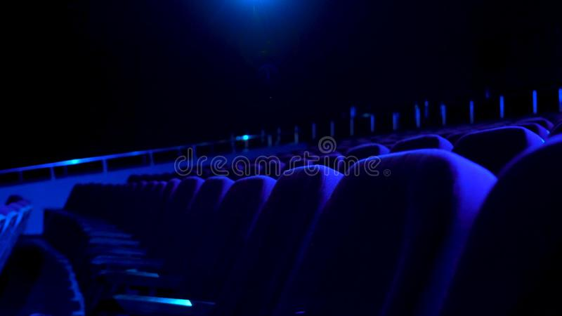 Dark, empty cinema hall with comfortable seats in blue light. Close up for seat rows in movie theatre. Dark, empty cinema hall with comfortable seats in blue royalty free stock photo