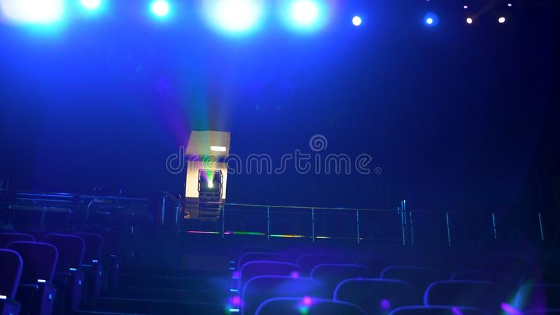 Dark, empty cinema hall with comfortable seats in blue light, projector, and bright spotlights. Close up for seat rows. In movie theatre stock photo