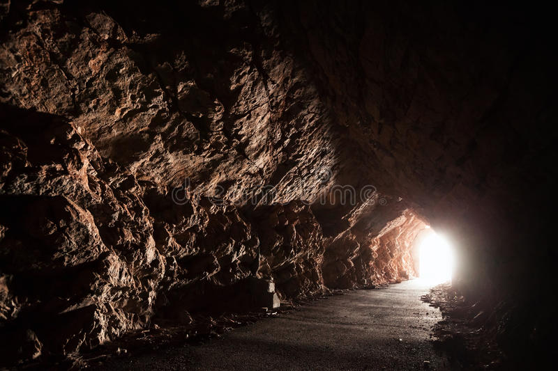 Dark empty road goes through the cave stock photo