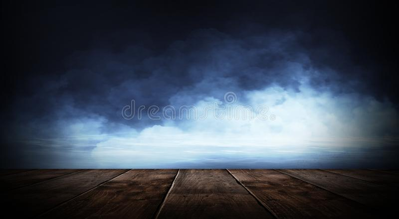 Dark empty room with brick walls and neon lights, smoke, rays. Brick wall, concrete and wooden table stock photos