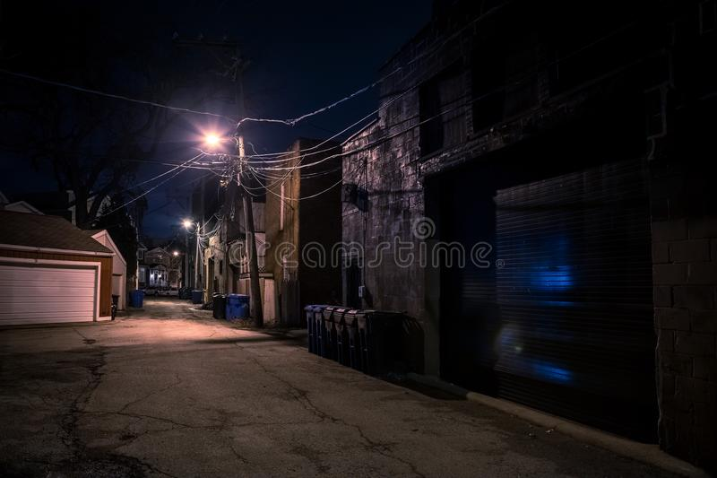 Dark empty and scary urban city street alley at night. Dark empty and scary urban city street alley with vintage buildings and garbage cans at night stock image