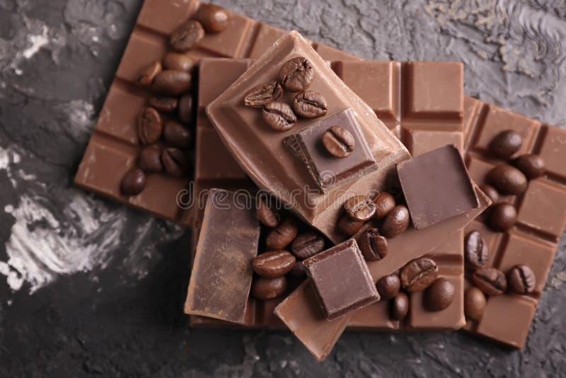 Dark en melkchocola met koffiebonen op grijze geweven achtergrond royalty-vrije stock foto