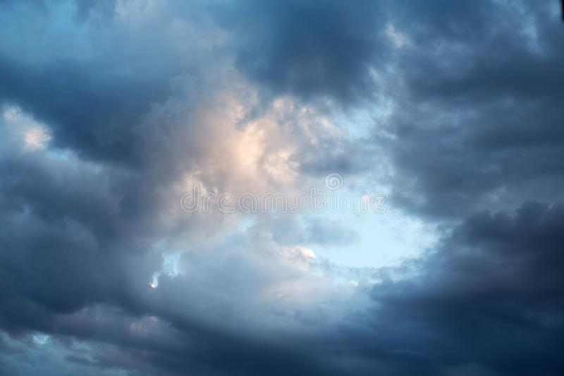 Dark evening cumulus clouds. In the setting sun royalty free stock image