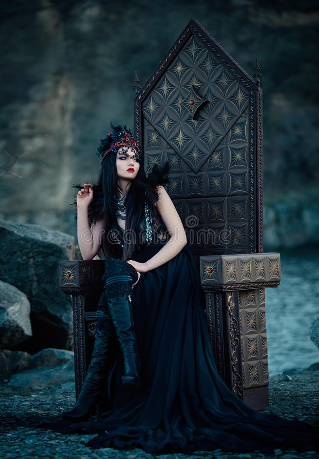 Dark evil queen. Sitting on a luxurious throne,snow white, wild Princess , vampire , hip toning , creative color,dark boho stock photography
