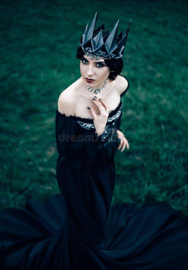 A dark evil queen. Sneaks through the blooming gardens, white wild Princess, vampire, thigh toning, creative color, dark bohemian stock image
