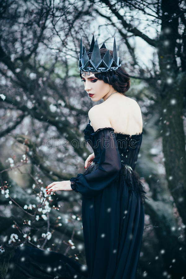 A dark evil queen. Sneaks through the blooming gardens, white wild Princess, vampire, thigh toning, creative color, dark bohemian stock images
