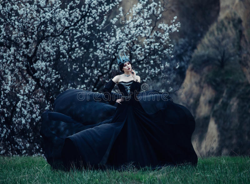 A dark evil queen. Sneaks through the blooming gardens, white wild Princess, vampire, thigh toning, creative color, dark bohemian royalty free stock photography