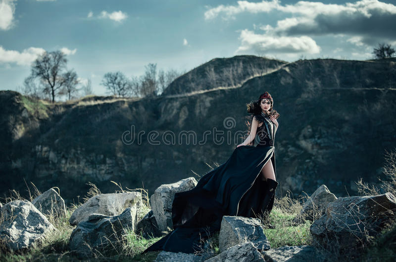 Dark evil queen. Sneaks through the stone canyon at cosplay movie snow white and the Huntsman wild Princess , vampire , hip toning , creative color,dark boho stock photography