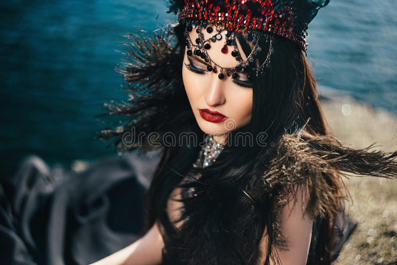 Dark evil queen. Sneaks through the stone canyon at cosplay moviesnow white, wild Princess , vampire , hip toning , creative color,dark boho royalty free stock image