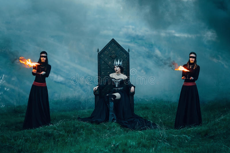 Dark evil queen. Sneaks through the stone canyon, fire lady sitting on a black gothic throne surrounded by servants, wild Princess, vampire, thigh toning royalty free stock photos