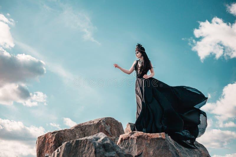 Dark evil queen. Sneaks through the stone canyon, wild Princess , vampire , hip toning , creative color,dark boho stock photo