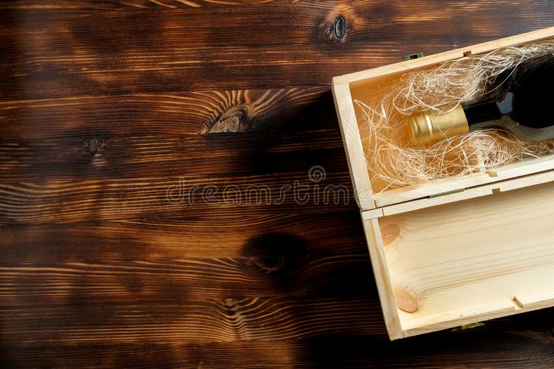A dark expensive bottle of wine in a wooden box on a wooden background royalty free stock images