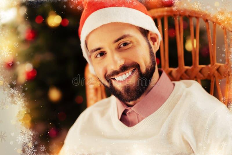 Dark-eyed bearded man feeling extremely cheerful before celebrating New year royalty free stock images